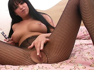 Solo cutie in fishnet stockings plays with her glass sex toy